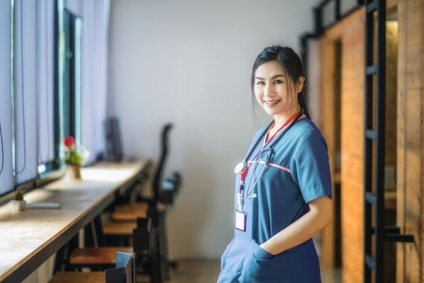 Side view of a female Asian American Nurse smiling with her hands in the pockets of her scrubs