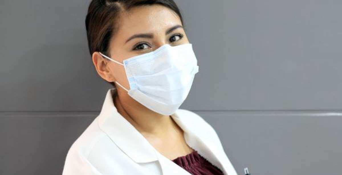 masked nurse looking into camera