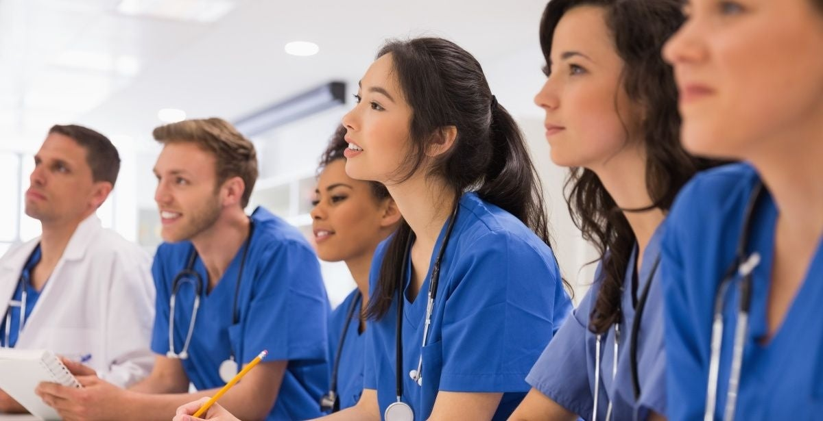 Nurses in blue scrubs writing an exam