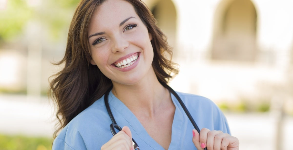 Smiling female nurse outdoors wearing a stethoscope