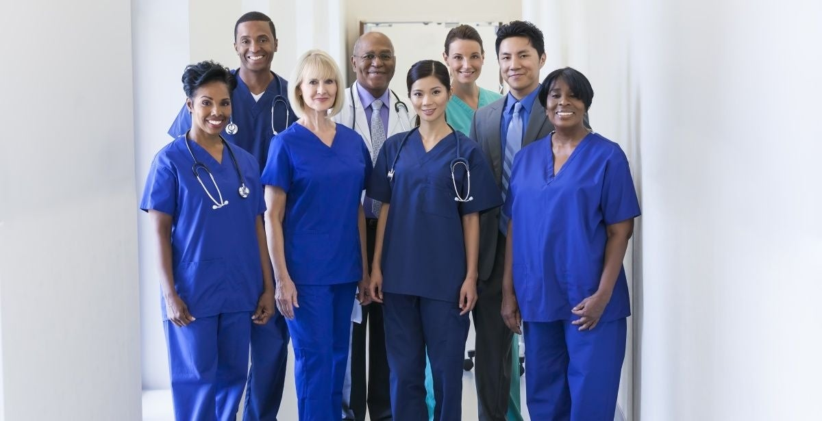 Group of ethnically diverse nurses standing and smiling in blue scrubs with other healthcare professionals