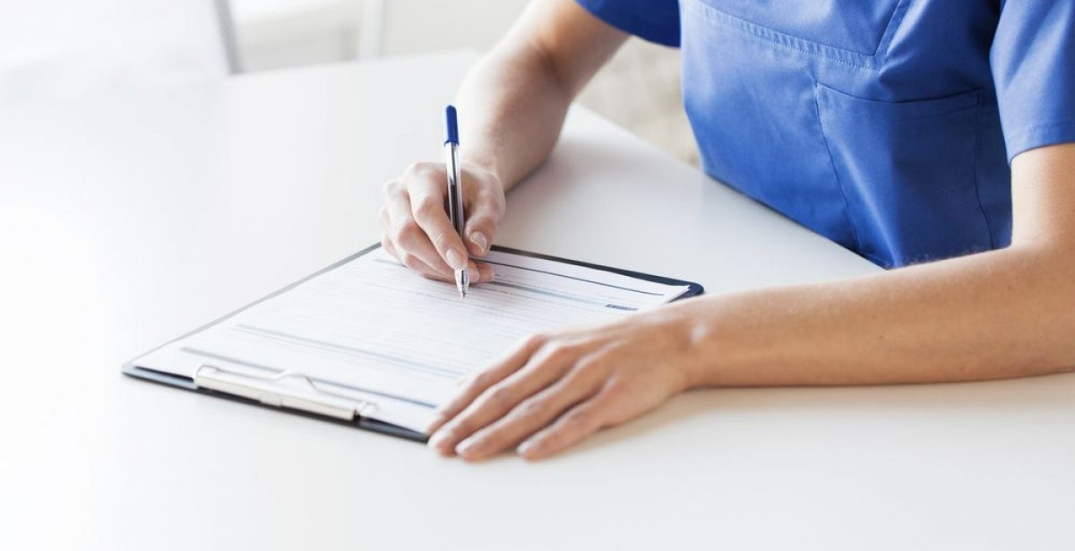 Nurse writing on clipboard at a desk