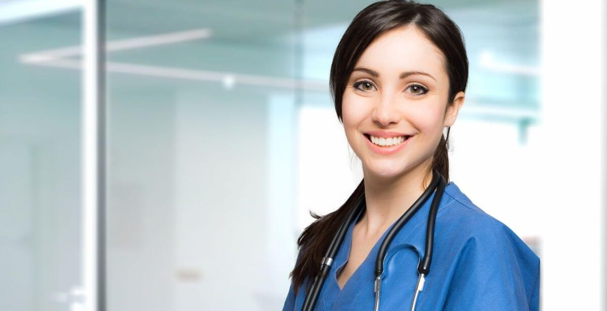 Close-up of smiling female nurse in blue scrubs