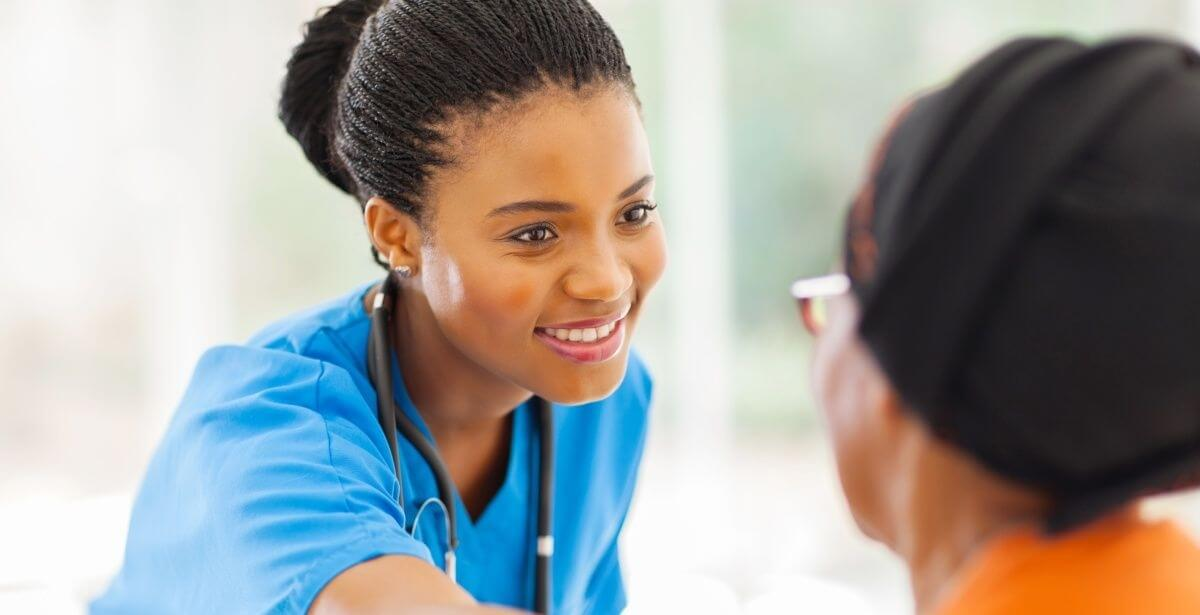 Smiling female African American nurse in blue scrubs comforting a female patient