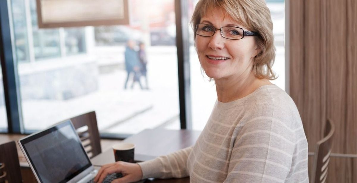 Middle-aged woman wearing glasses doing schoolwork in a library on a laptop