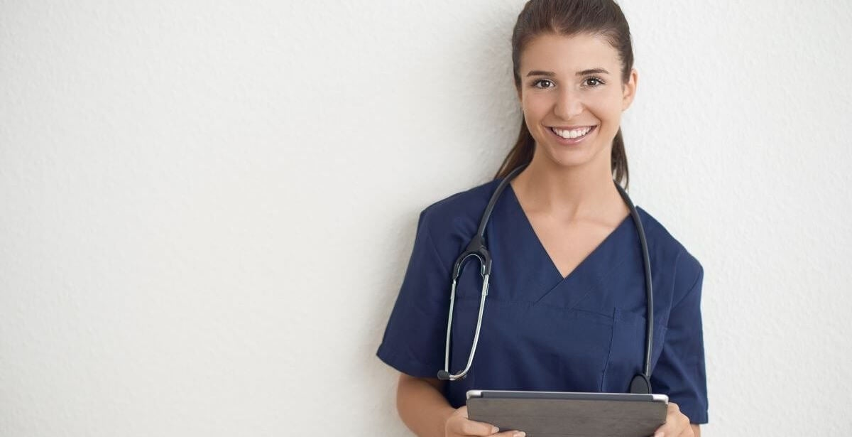 Smiling nurse wearing scrubs and using a tablet device against a white background