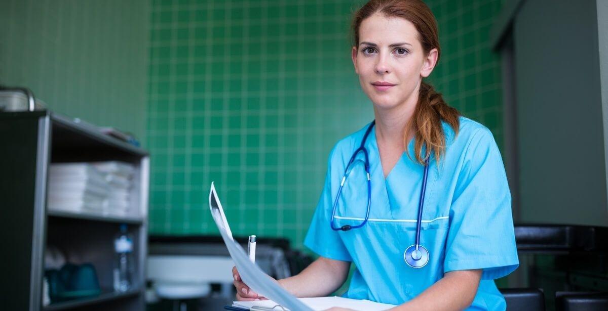Registered nurse filling out paperwork in a hospital room