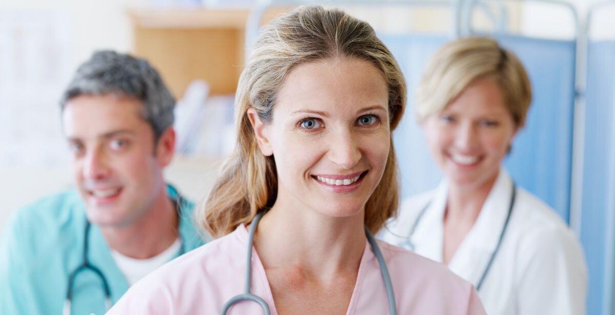 A group of three smiling nurses