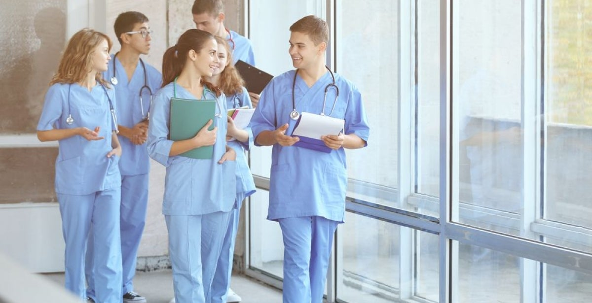 Group of young male and female nurses wearing scrubs