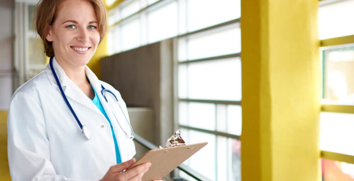 Smiling female nurse practitioner in a white lab coat taking notes by a brightly lit window